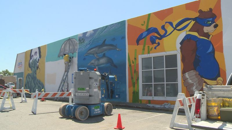 The wall features murals from eight local artists.