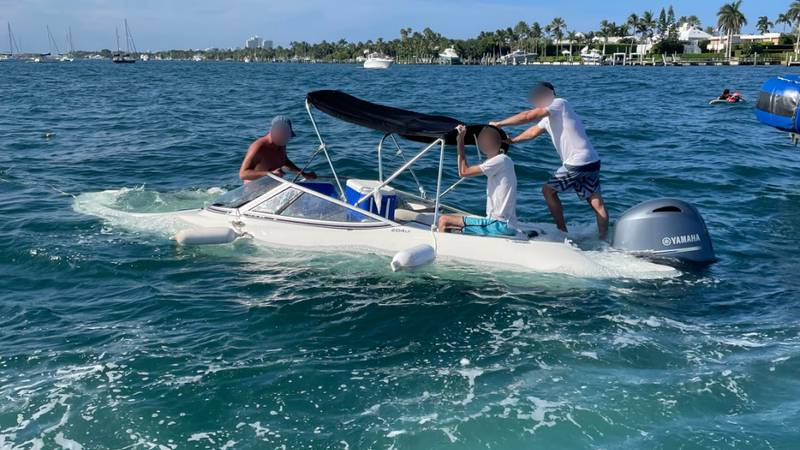 A U.S. Coast Guard Station Lake Worth Inlet rescue crew assists three crewmembers aboard a...