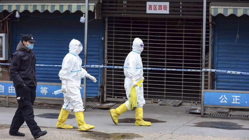 FILE - In this Jan. 27, 2020 file photo, workers in protective gear carry a bag containing a...