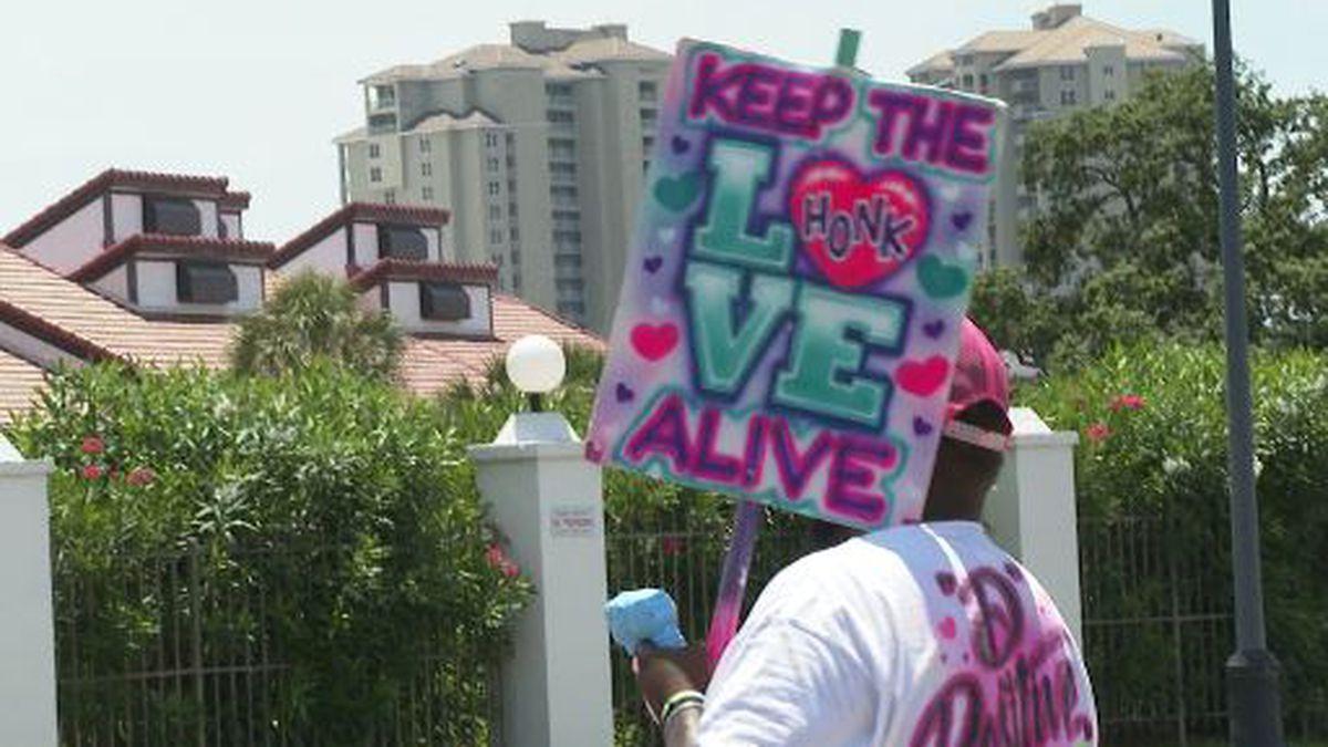 Decaris Hunter stood on the corner of Richard Jackson Boulevard and held signs encouraging...