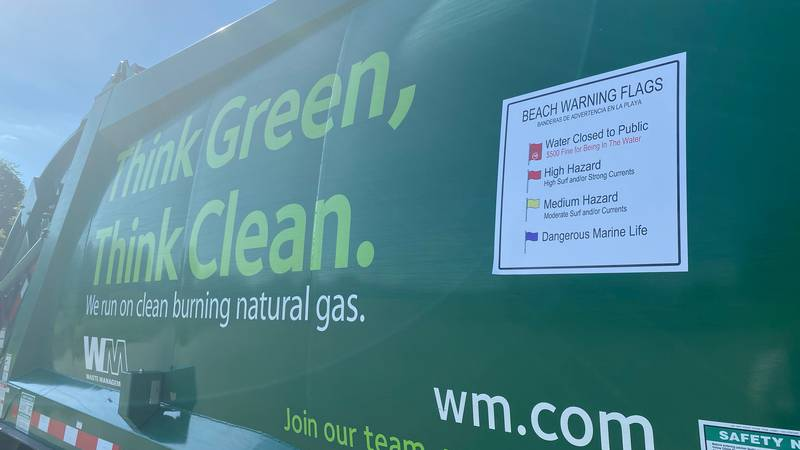 Beach warning flag signs are posted on Waste Management trucks in Walton County.