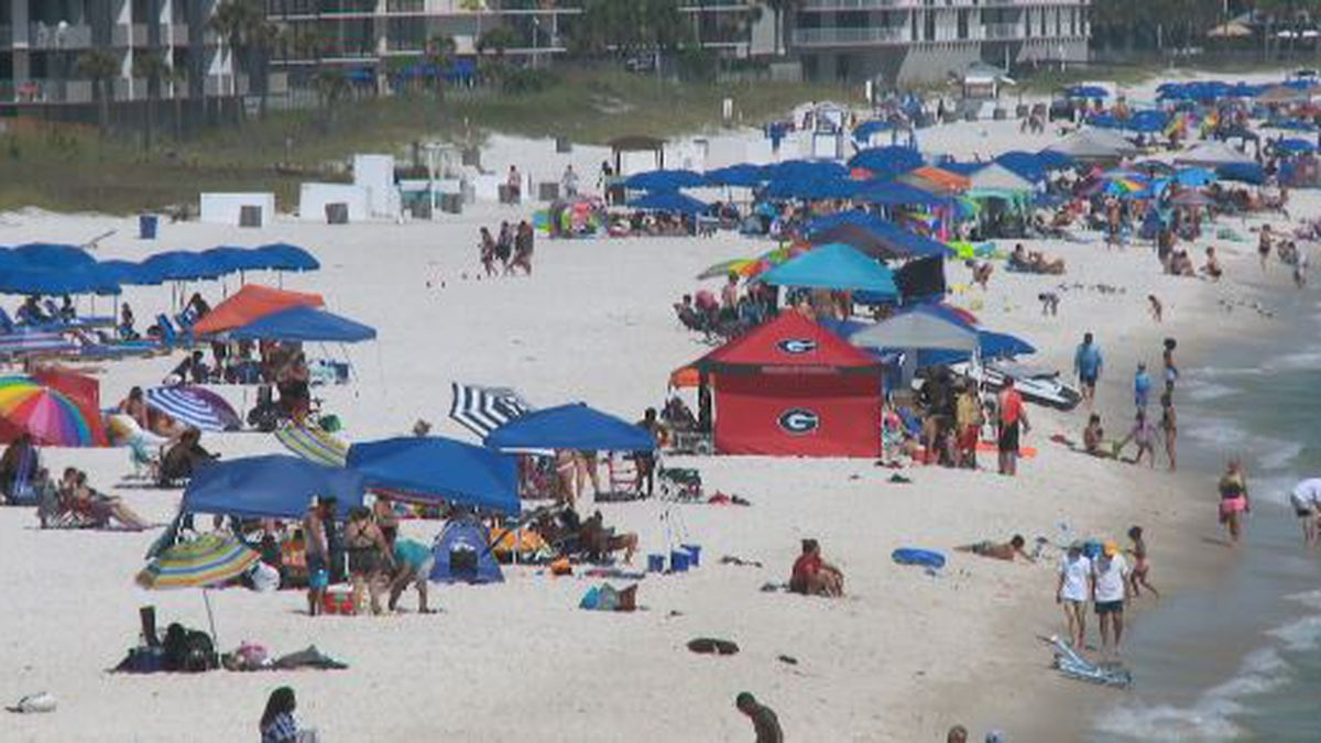 Locals and vacationers line the beach at the county pier on Sunday afternoon.