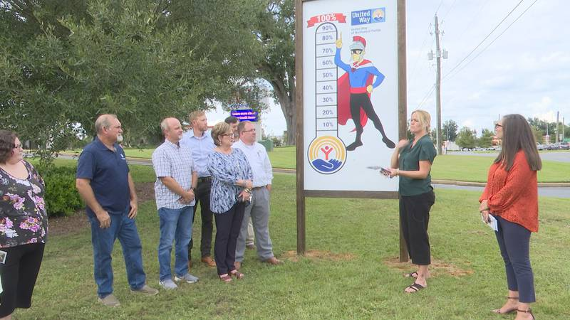 Members of the Jackson County Sheriff's Office helped dig the holes to erect the sign, and...