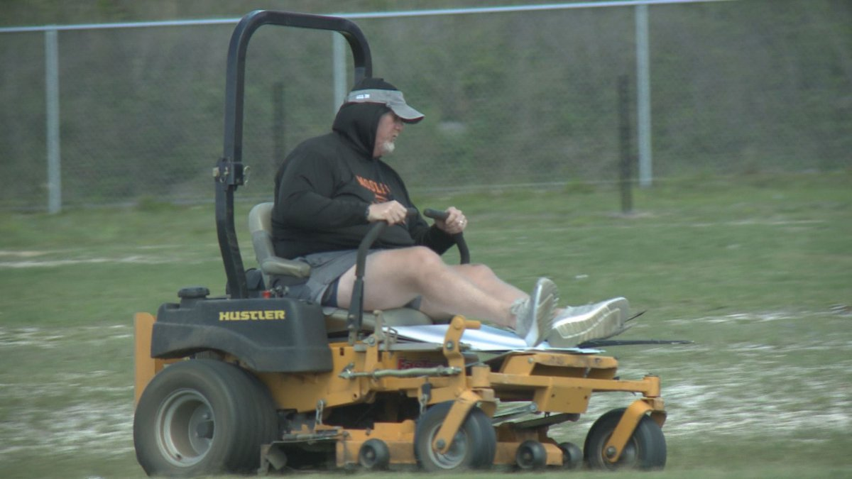 Mosley football coach Jeremy Brown still working on the field, and working with his players as...