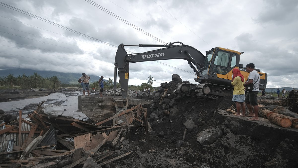 Residents watch as a backhoe clears boulders and mudflows from Mayon Volcano triggered by heavy...