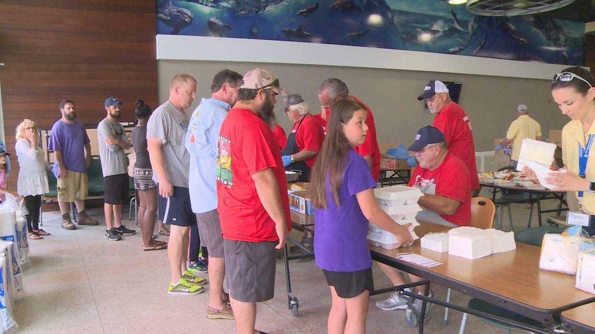 This image shows people being served barbecue by volunteers at the Operation BBQ Relief event...