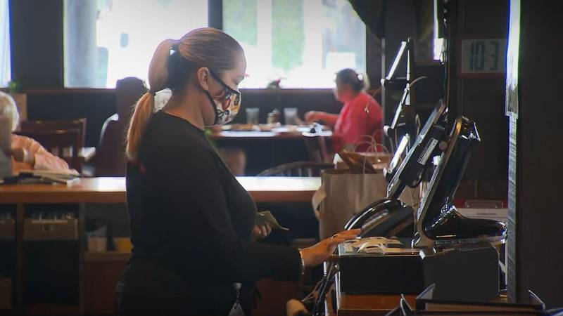 A restaurant staffer wears a face mask while working. The CDC is expected to release new...