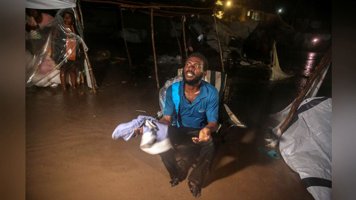 People affected by Saturday's earthquake attempt to take cover from the rain of Tropical...