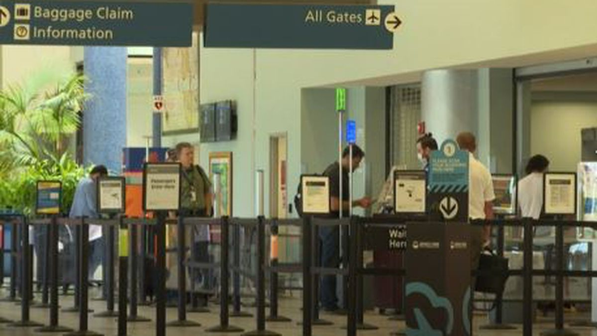 Travelers stand six feet apart on social distancing markers on the floor as they prepare to go through security at Northwest Florida Beaches International Airport. (WJHG/WECP)