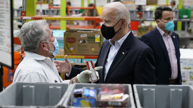 President Joe Biden talks with a volunteer at the Houston Food Bank, Friday, Feb. 26, 2021, in...