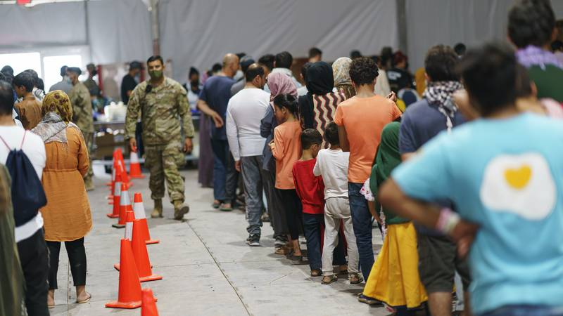 Afghan refugees line up for food in a dining hall at Fort Bliss' Doña Ana Village, in New...