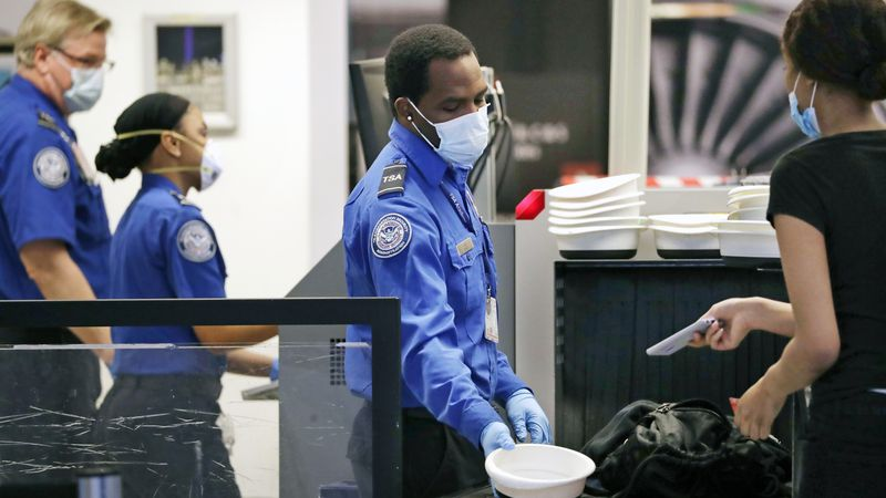 TSA officers wear protective masks at a security screening area at Seattle-Tacoma International...