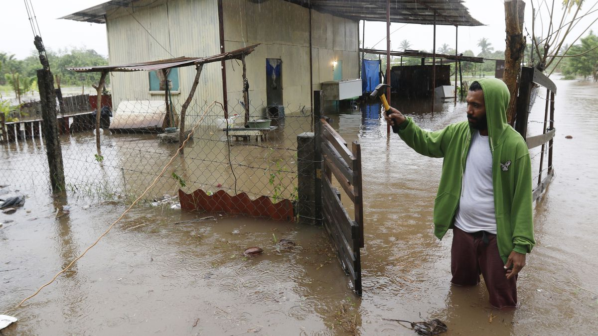 A resident repairs a gate while standing in knee-deep floodwaters outside his home in Jehova,...