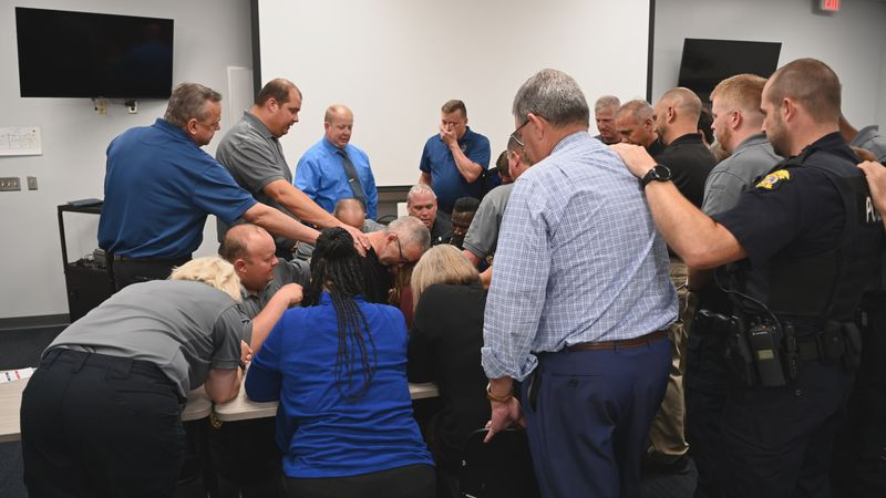 Panama City Police Department officers pray over one of their own after he is diagnosed with a...
