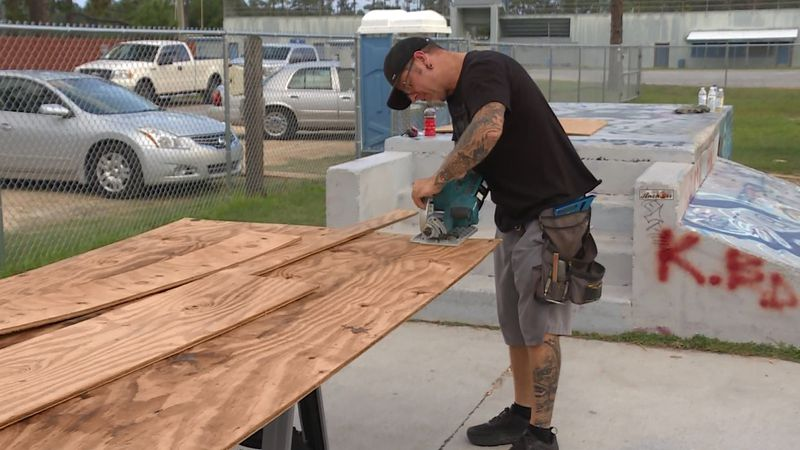 Ernie Watkins cuts a piece of plywood to be used as part of a skate ramp.